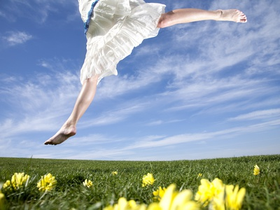 young-woman-in-park-jumping-on-lawn